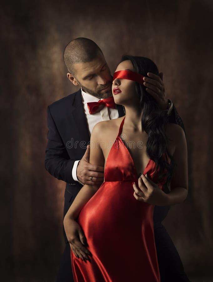 Pares no amor, mulher 'sexy' da forma e homem, menina com a faixa vermelha nos olhos que encantam o noivo no terno, encanto Portr foto de stock