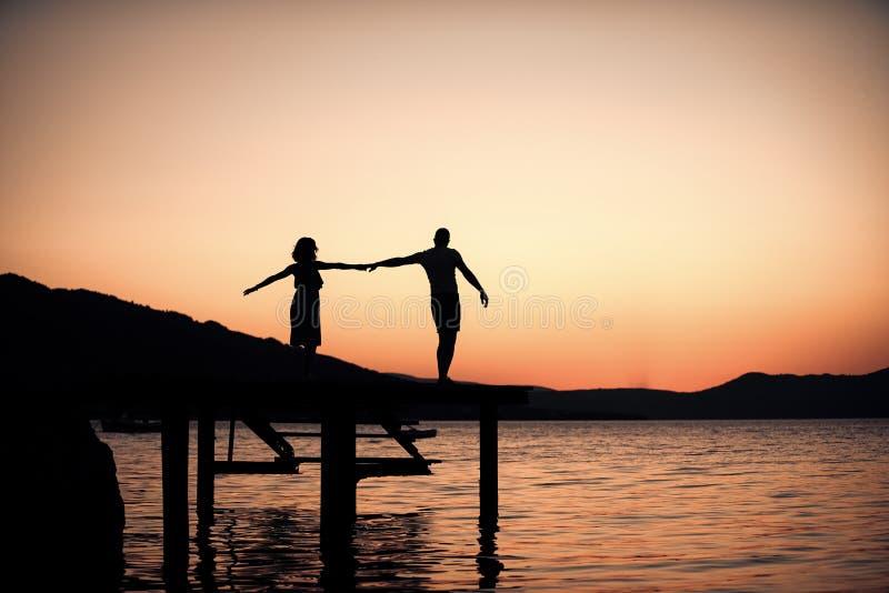 Pares no amor na data romântica na noite na doca, espaço da cópia Conceito do romance e do amor Silhueta de pares sensuais imagem de stock