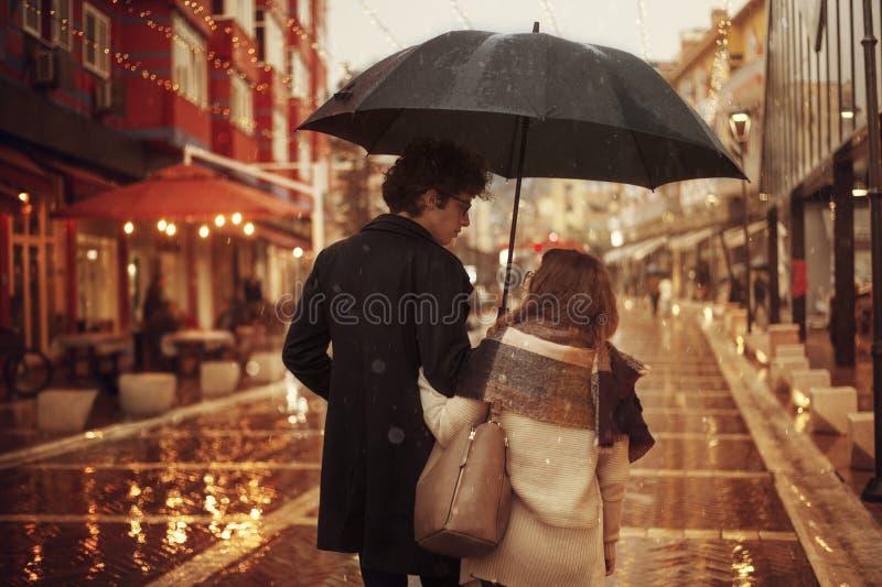 Pares no amor na rua em um dia chuvoso Amigos que andam abaixo da rua fotografia de stock royalty free