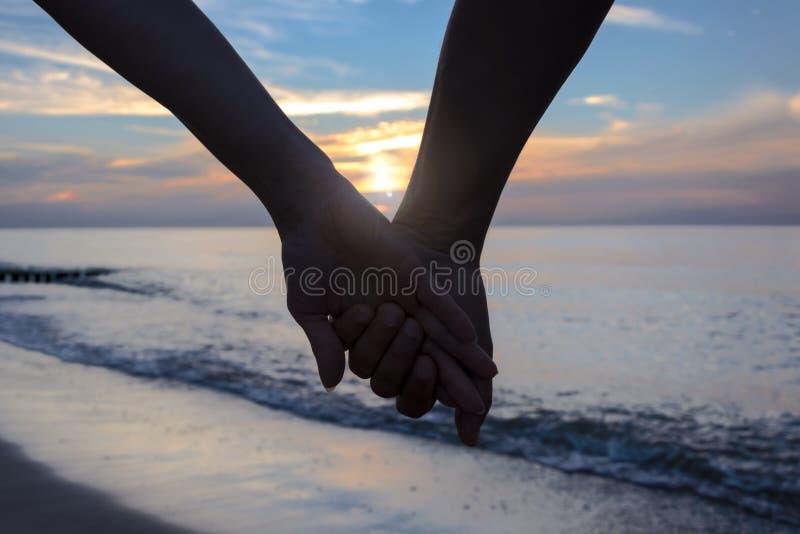 Pares no amor pelo mar no por do sol imagem de stock