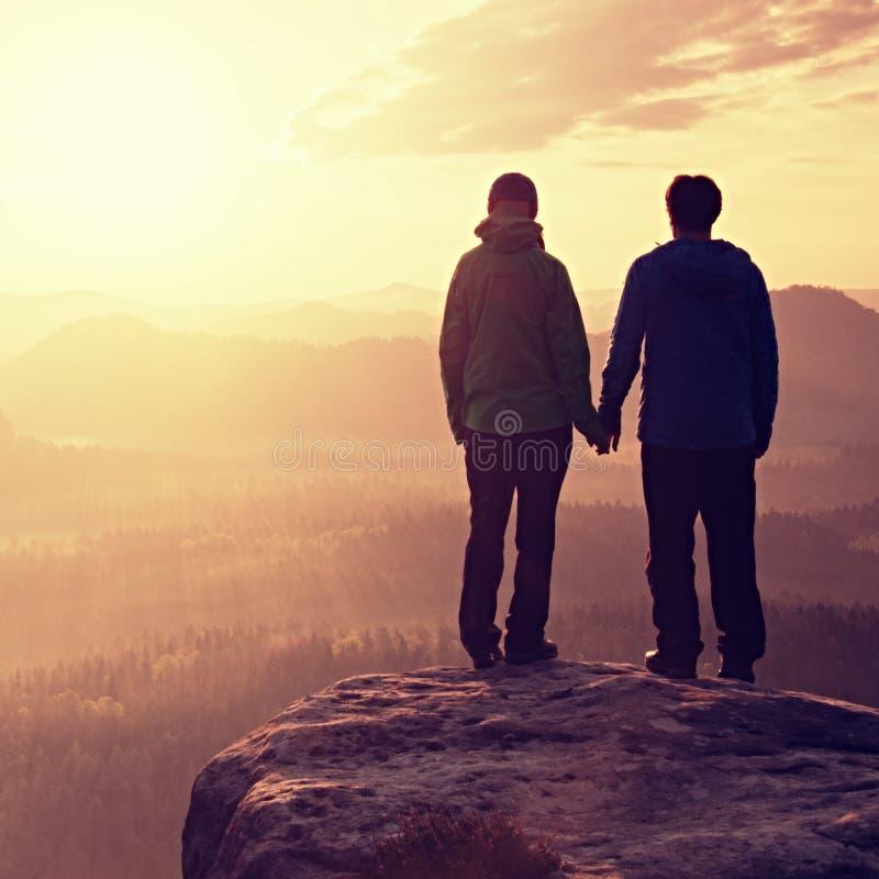 Pares no amor que aprecia momentos macios durante o por do sol Os pares novos de caminhantes em conjunto no pico de impérios da r fotos de stock royalty free
