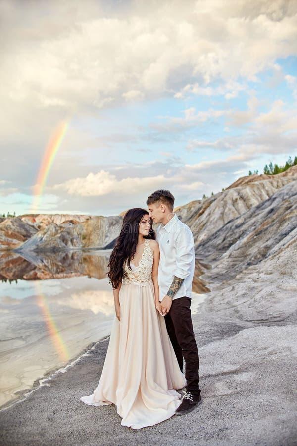 Pares no amor que beija e que abraça no fundo do arco-íris e das montanhas Um homem e um amor da mulher fabulous imagens de stock royalty free