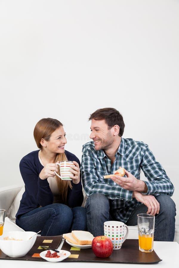 Pares no amor que come um café da manhã imagem de stock