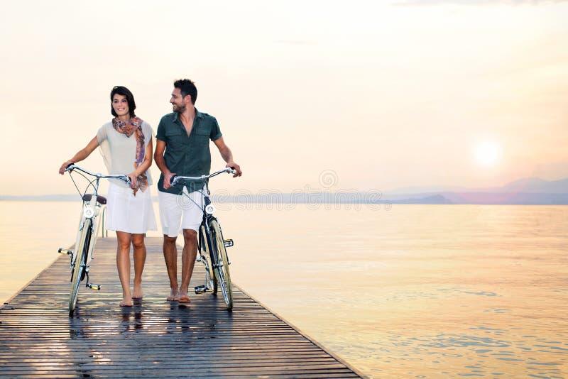 Pares no amor que empurra a bicicleta em um passeio à beira mar no mar fotografia de stock