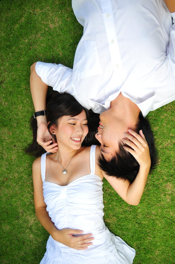 Pares no amor que encontra-se na grama imagem de stock royalty free