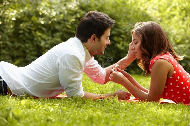 Pares no amor que encontra-se na grama no parque imagens de stock royalty free
