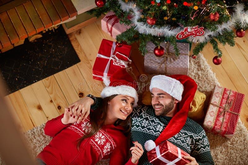 Pares no amor que encontra-se sob a árvore de Natal foto de stock royalty free