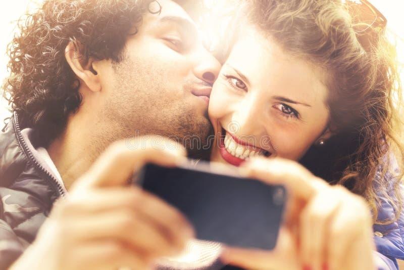 Pares no amor que faz um selfie quando ele que dá lhe um beijo imagem de stock royalty free