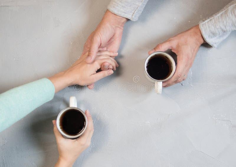 Pares no amor que guarda as mãos com café na tabela de mármore branca Fotografe tomado de cima de, vista superior com espaço da c foto de stock royalty free