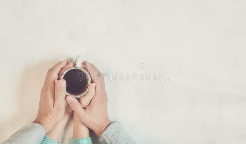 Pares no amor que guarda as mãos com café na tabela de mármore branca Fotografe tomado de cima de, vista superior com espaço da c fotografia de stock royalty free