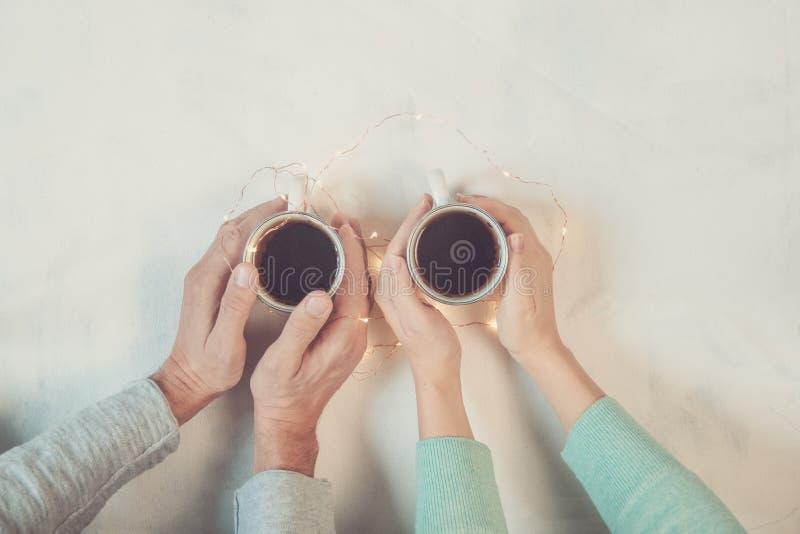 Pares no amor que guarda as mãos com café na tabela de mármore branca Fotografe tomado de cima de, vista superior com espaço da c foto de stock