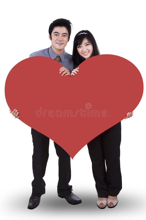 Pares no amor que guarda um coração vermelho grande imagens de stock