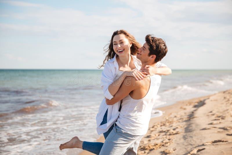 Pares no amor que ri e que tem o divertimento na praia foto de stock
