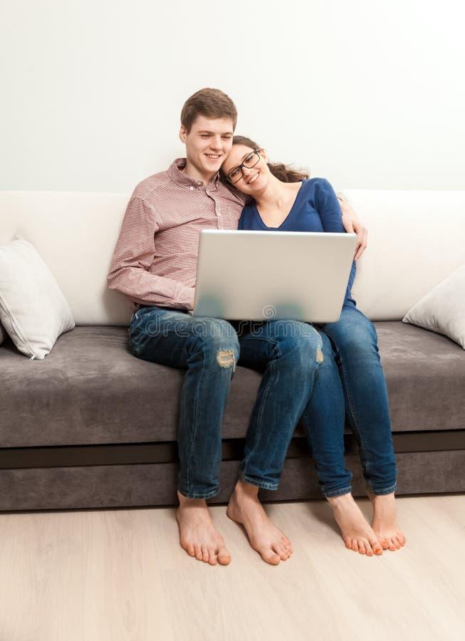 Pares no amor que senta-se no sofá e no filme de observação no portátil foto de stock
