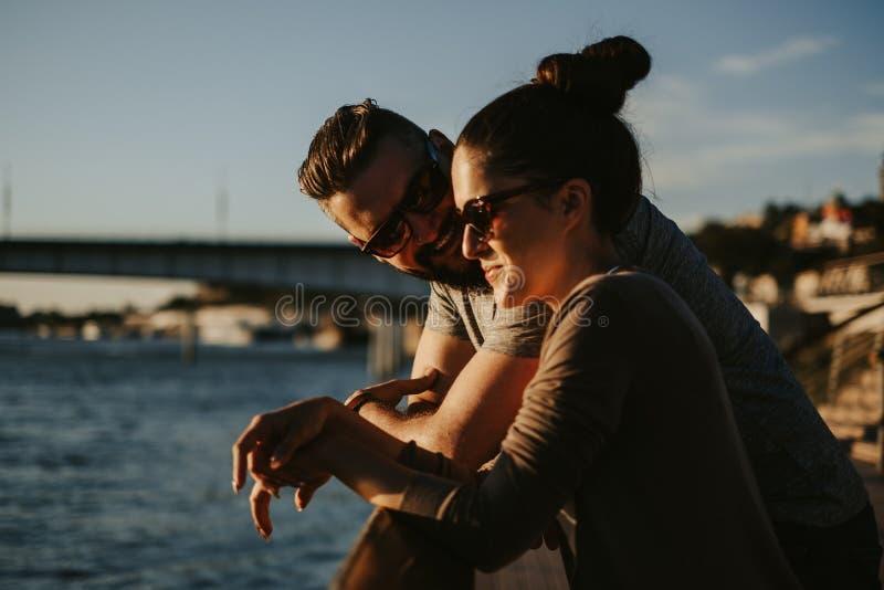Pares no amor que sorri no por do sol pelo rio imagens de stock