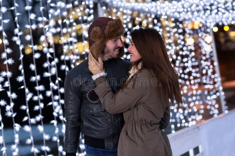 Pares no amor que tem o divertimento na pista de gelo imagens de stock royalty free
