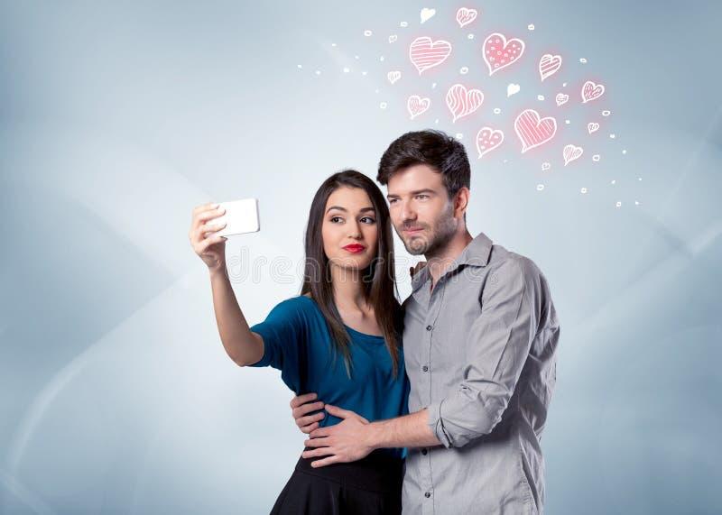 Pares no amor que toma o selfie com coração vermelho fotos de stock royalty free