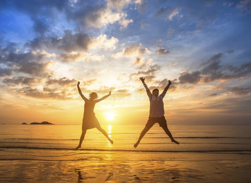 Pares no amor a saltar acima na praia durante um por do sol impressionante felicidade imagens de stock royalty free