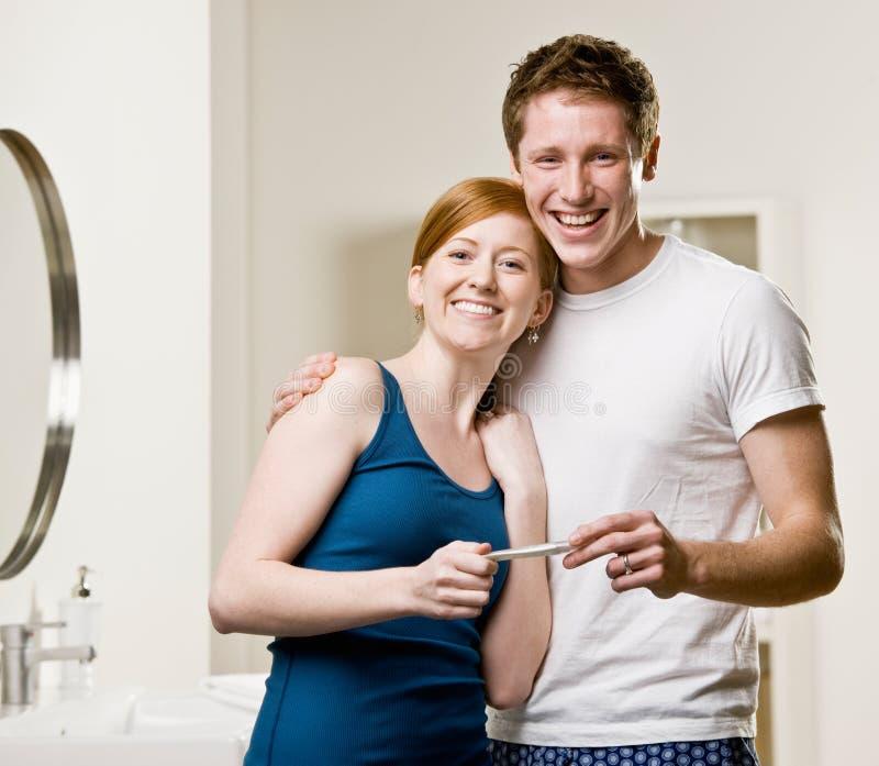 Pares no banheiro que vê tes positivos da gravidez foto de stock