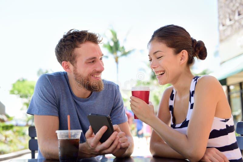 Pares no café que olha imagens espertas do app do telefone fotografia de stock