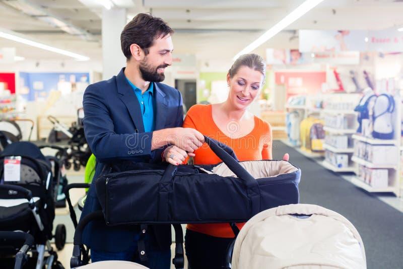 Pares no carrinho de criança da compra de loja do bebê imagens de stock royalty free