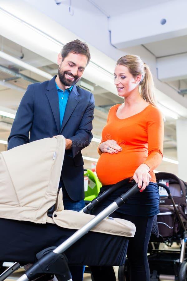 Pares no carrinho de criança da compra de loja do bebê imagem de stock royalty free
