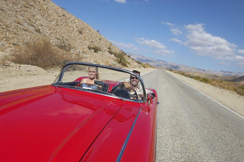 Pares no carro clássico na estrada do deserto fotografia de stock