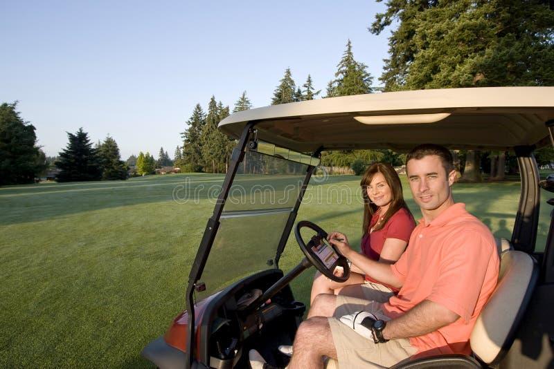 Pares no carro no campo de golfe - horizontal imagens de stock