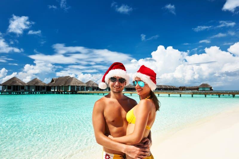 Pares no chapéu de Santa em uma praia em Maldivas imagem de stock royalty free