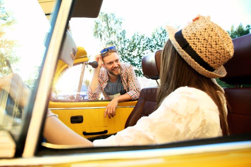 Pares no convertible Pares novos bonitos que apreciam a viagem por estrada no convertible e que olham se com sorriso fotos de stock royalty free
