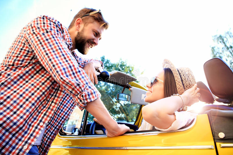 Pares no convertible Pares novos bonitos que apreciam a viagem por estrada no convertible e que olham se com sorriso foto de stock royalty free