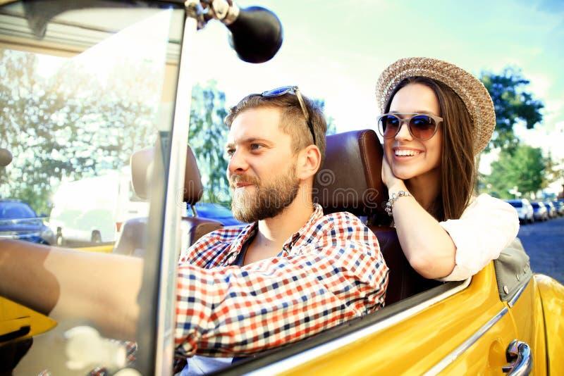Pares no convertible Pares novos bonitos que apreciam a viagem por estrada no convertible e que olham se com sorriso foto de stock