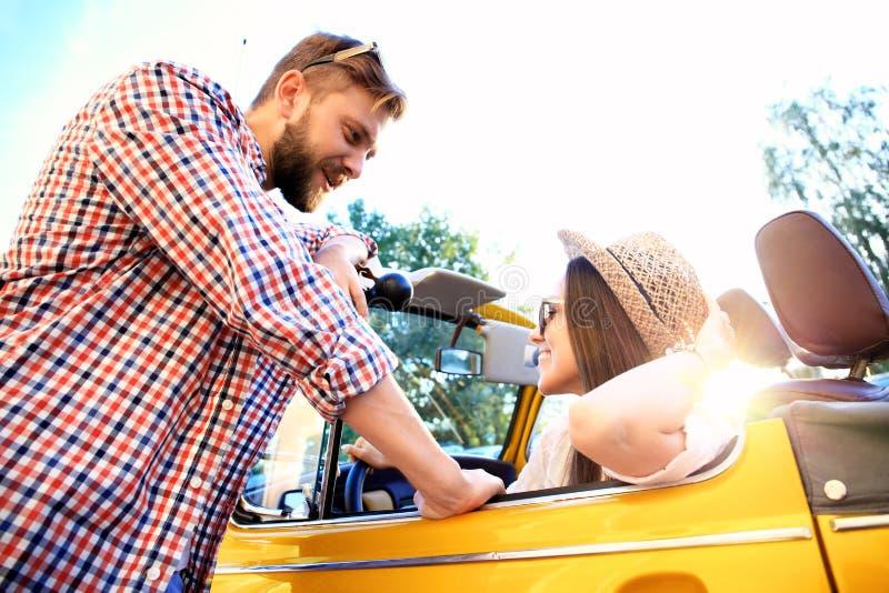 Pares no convertible Pares novos bonitos que apreciam a viagem por estrada no convertible e que olham se com sorriso fotografia de stock royalty free