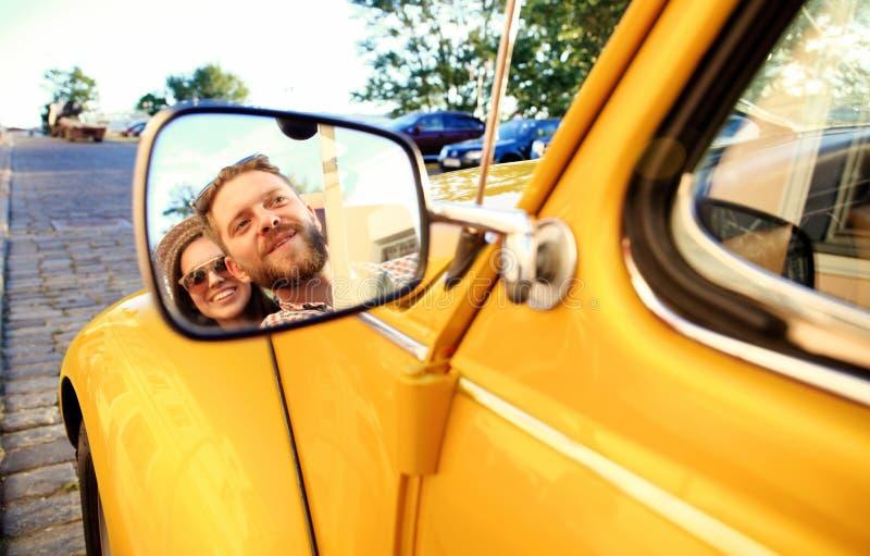 Pares no convertible Pares novos bonitos que apreciam a viagem por estrada no convertible e que olham se com sorriso imagem de stock royalty free