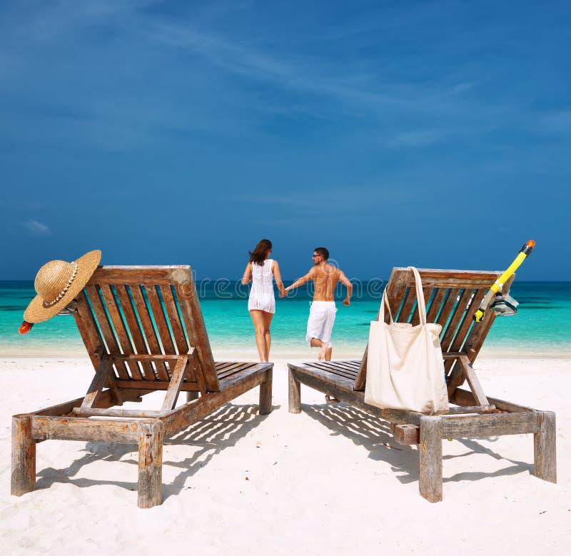 Pares no corredor branco em uma praia em Maldivas fotografia de stock royalty free