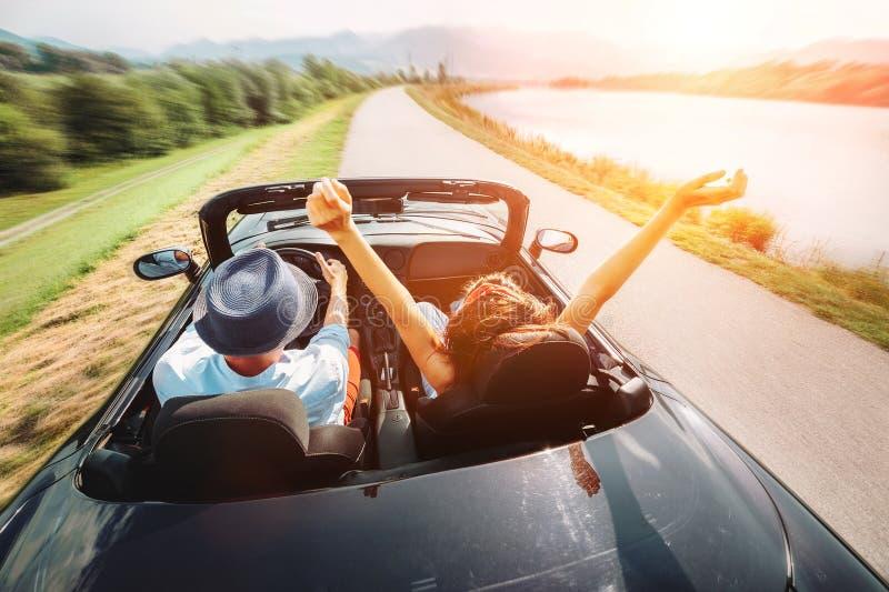 Pares no passeio do amor no carro do cabriolet fotografia de stock