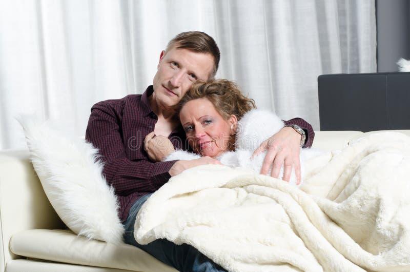 Pares no sofá - é doente imagens de stock royalty free