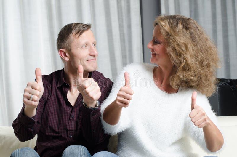 Pares no sofá com polegares acima imagens de stock royalty free