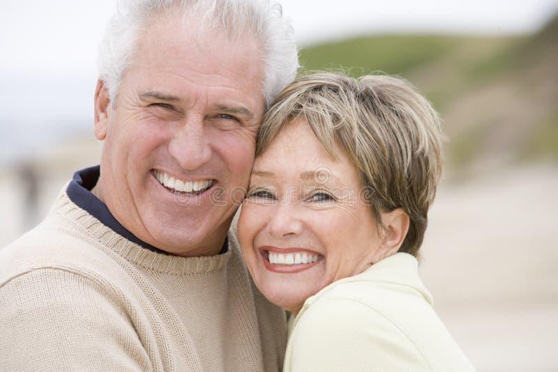 Pares no sorriso da praia imagem de stock