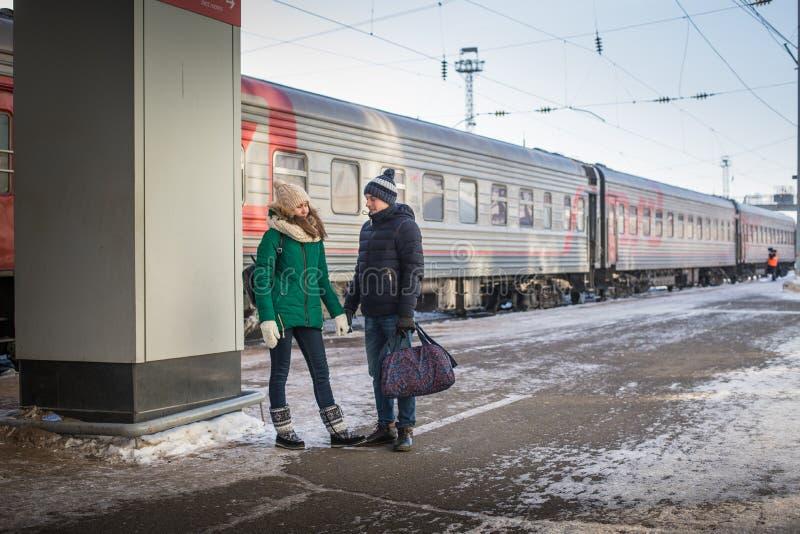 Pares no trem próximo da estação de trem em uma estadia de inverno imagem de stock