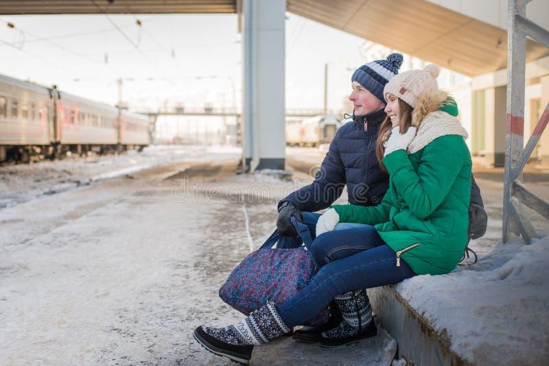 Pares no trem próximo da estação de trem em uma estadia de inverno foto de stock