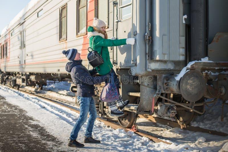 Pares no trem próximo da estação de trem em uma estadia de inverno imagens de stock