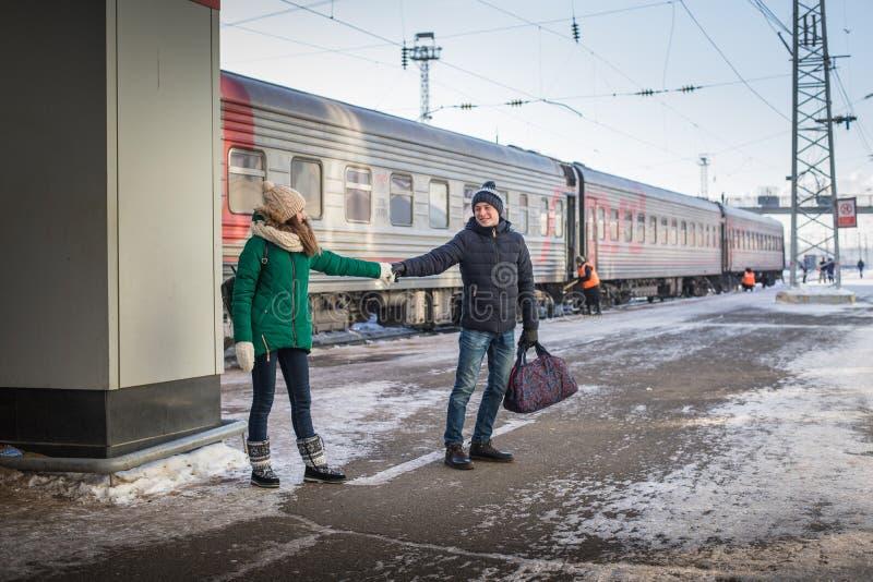 Pares no trem próximo da estação de trem em uma estadia de inverno foto de stock royalty free