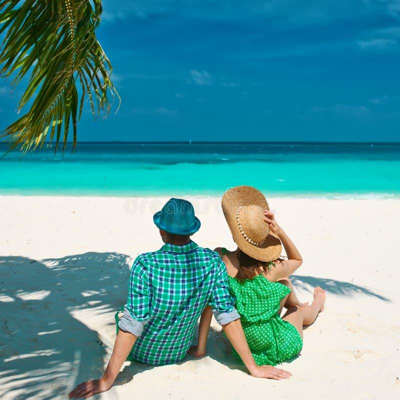 Pares no verde em uma praia em Maldivas fotografia de stock