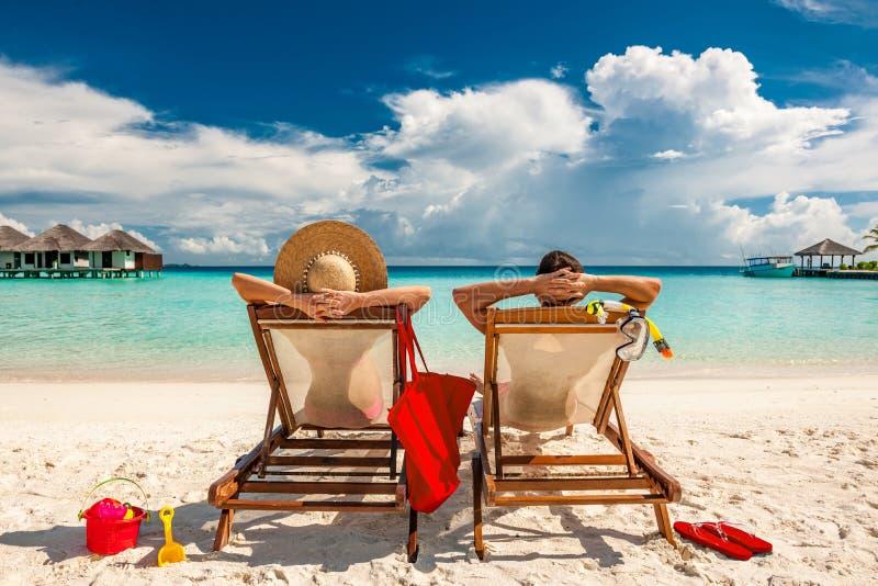 Pares nos vadios na praia em Maldivas imagem de stock royalty free