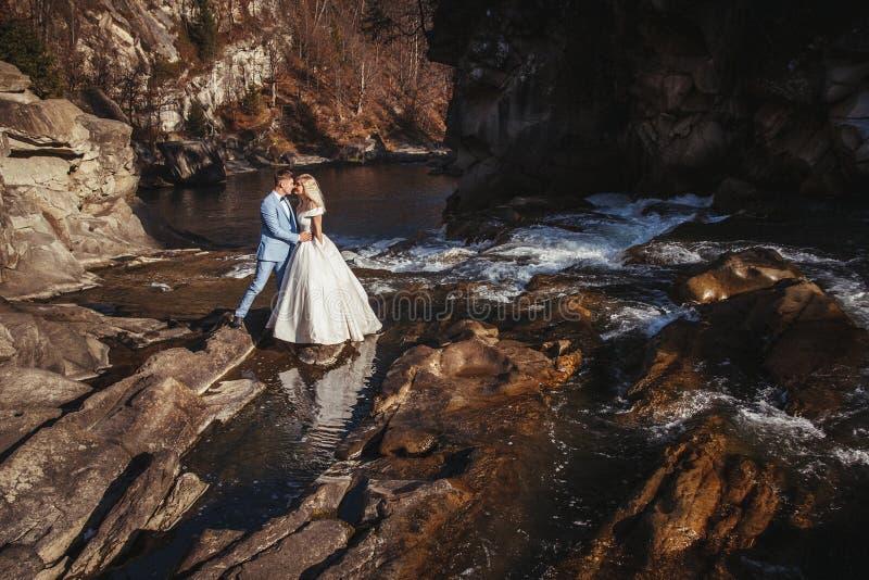 Pares, novia asombrosa y novio de la boda llevando a cabo las manos en montañas y fondo de los ríos Muchacha linda en la alineada imagen de archivo