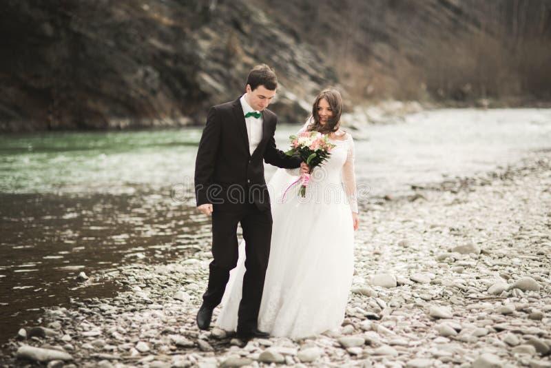 Pares, novia feliz y novio de la boda presentando el río aseado contra el contexto de las montañas imagenes de archivo