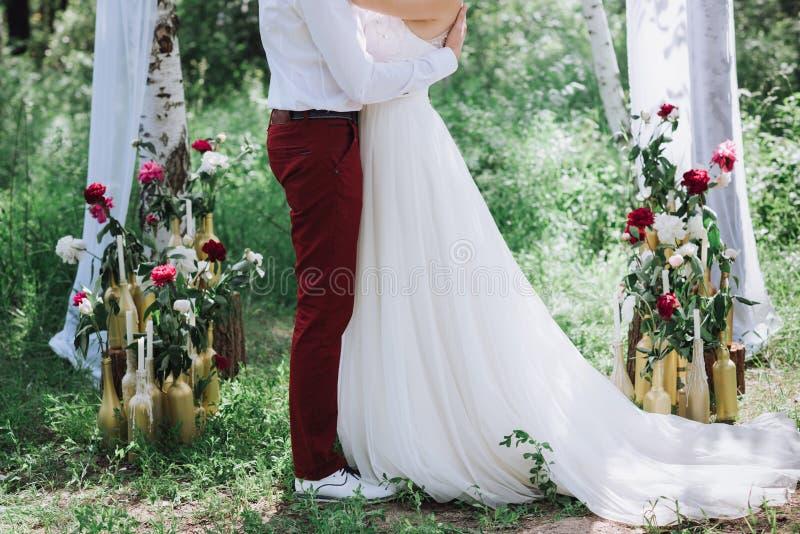 Pares, novia y novio hermosos jovenes en el bosque contra la perspectiva de la decoración de la boda imagen de archivo libre de regalías