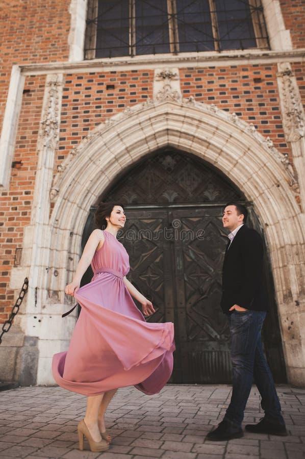 Pares, novio magnífico y novia de la boda con el vestido rosado caminando en la ciudad vieja de Kraków foto de archivo libre de regalías