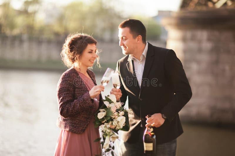 Pares, novio y vestido de la boda presentando cerca del río con un vidrio en la puesta del sol imagen de archivo